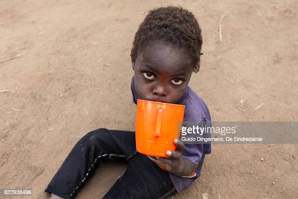 thirsty boy with cup of water (malawi, 2016) - hongerig stockfoto's en -beelden