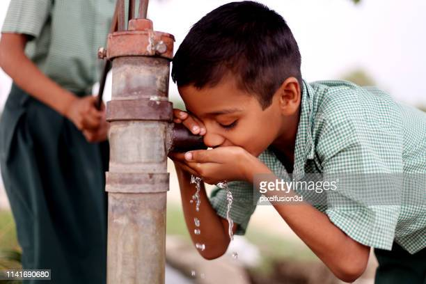thirsty child drinking water on water pump - drinking water stock pictures, royalty-free photos & images
