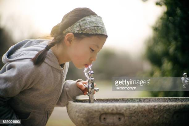 Thirsty girl drinking water from fountain