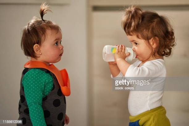 thirsty little girl - milk bottle stock pictures, royalty-free photos & images