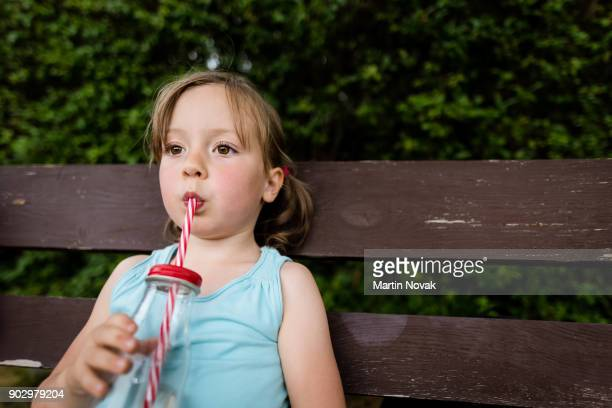 Thirsty little girl sipping water from straw