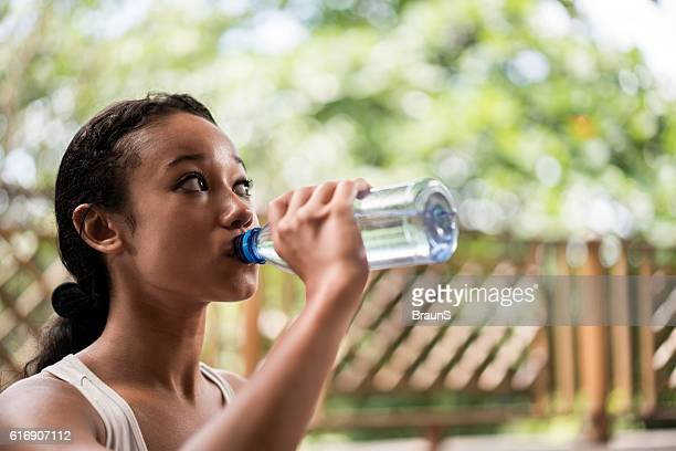 Thirsty Malaysian woman drinking fresh water from the bottle.
