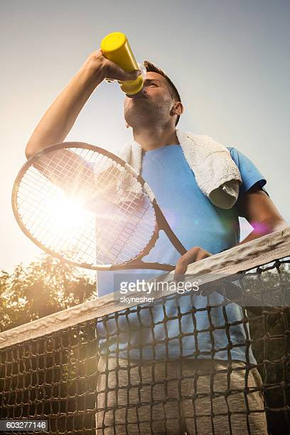 Thirsty tennis player drinking water after the match.