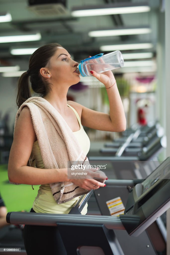 Thirsty woman in a gym drinking water from a bottle stock photo thirsty woman in a gym drinking water from a bottle stock photo sciox Choice Image