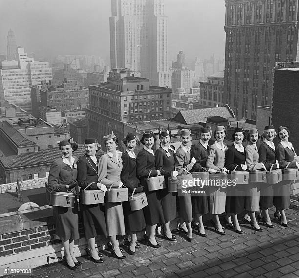 Thirteen of the twentyone air stewardesses who are competing for the 'Miss Skyway' Award pose on the Biltmore Hotel roof against the familiar New...