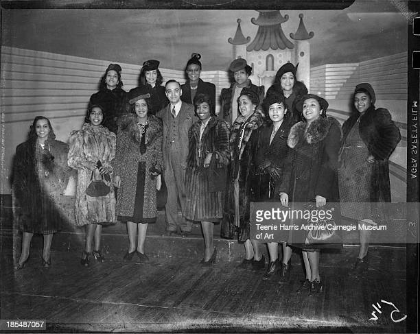 Thirteen women including one wearing herringbone coat with fur collar dark suit large round pendant necklace and dark hat with fur trim and...