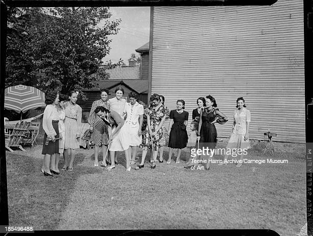Thirteen women most members of the We'Uns Club in Wilnette Brooks Jones' yard on Susquehanna Street Pittsburgh Pennsylvania 1941 Including Mrs Clyde...