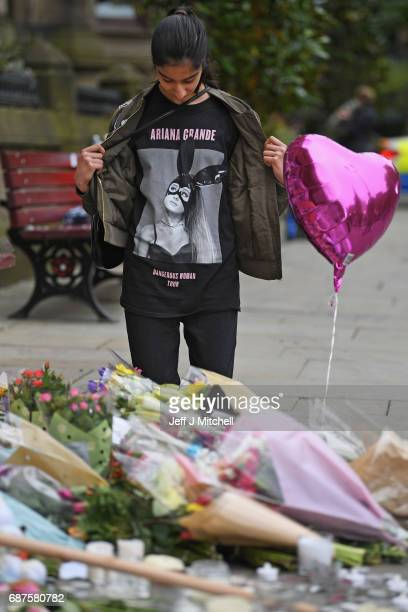 Thirteen year old Iqra Saied who attended the Ariana Grande concert looks at floral tributes and messages as the working day begins on May 24 2017 in...