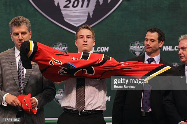 Thirteenth overall pick Sven Baertschi by the Calgary Flames puts on a Calgary Flames jersey onstage during day one of the 2011 NHL Entry Draft at...