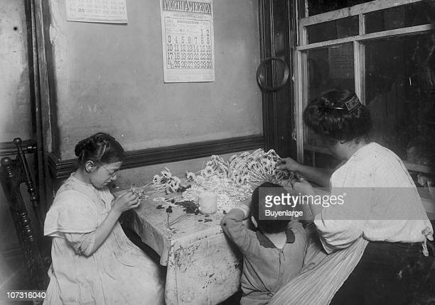 A thirteenyearold girl works with her aunt as they make flowers in a tenement room New York New York 1911