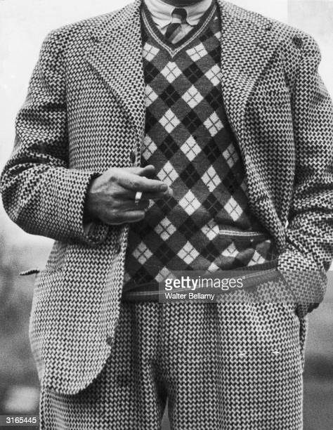 A thirties golfer wearing a Vneck pullover which clashes with his checked jacket and plus fours