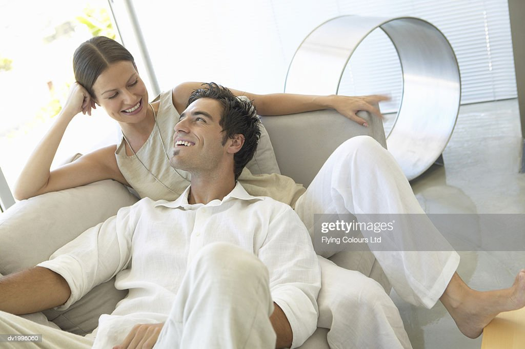 Thirty something Couple Sitting on a Sofa in a Modern Living Room : Stock Photo