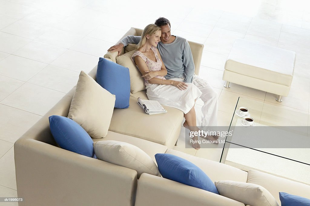 Thirty something Couple Sitting Side By Side on a Sofa : Stock Photo