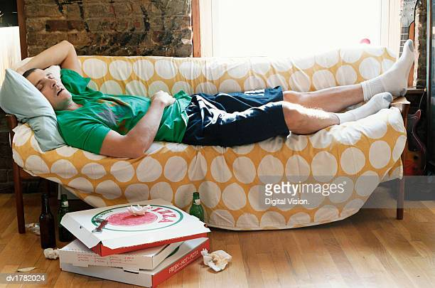 thirty something man lying asleep on a sofa in an apartment - laziness stock pictures, royalty-free photos & images