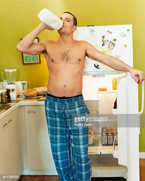 Thirty something Man Standing in a Kitchen With the Fridge Door Open Drinking From a Bottle Of Milk
