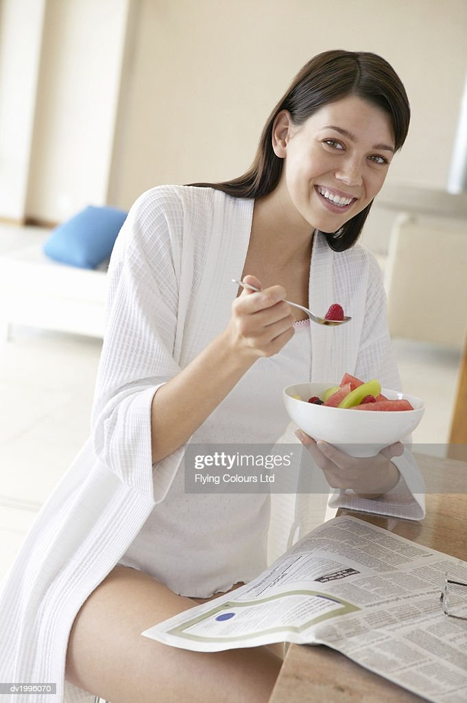 Thirty something Woman at Breakfast Eating a Bowl of Fruit at a Kitchen Counter : Stock Photo
