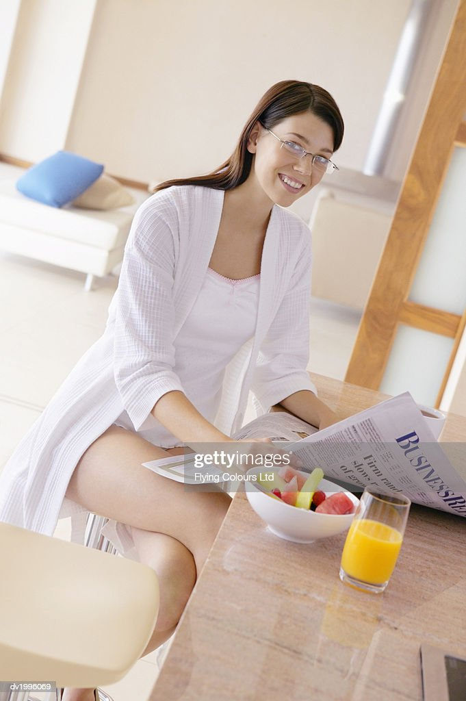Thirty something Woman at Breakfast Sitting on a Stool at a Kitchen Counter Holding a Newspaper : Stock Photo