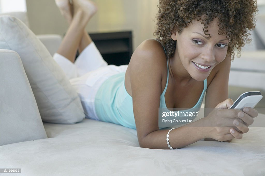 Thirty something Woman Lying on a Sofa Dialing on a Mobile Phone : Stock Photo