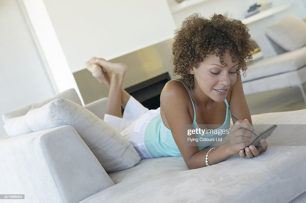 Thirty something Woman Lying on a Sofa Using a Handheld PC : Stock Photo