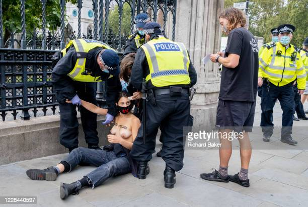 Thirty topless women supporters of Climate Change activists Extinction Rebellion protest outside the UK parliament railings on 10th September 2020 in...