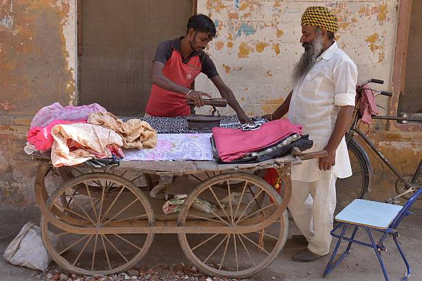 Thirty yearold presswallah Ramjass uses a charcoal iron to press clothes in Amritsar on October 5 2015 Ramjass charges 250 INR per piece and makes...
