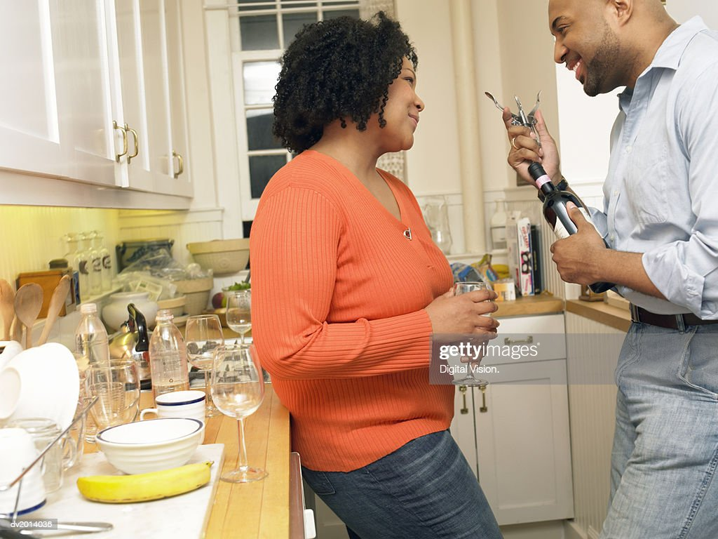 Thirtysomething Couple Stand in a Kitchen Talking and Smiling, the Man Opening a Bottle of Wine : Stock Photo