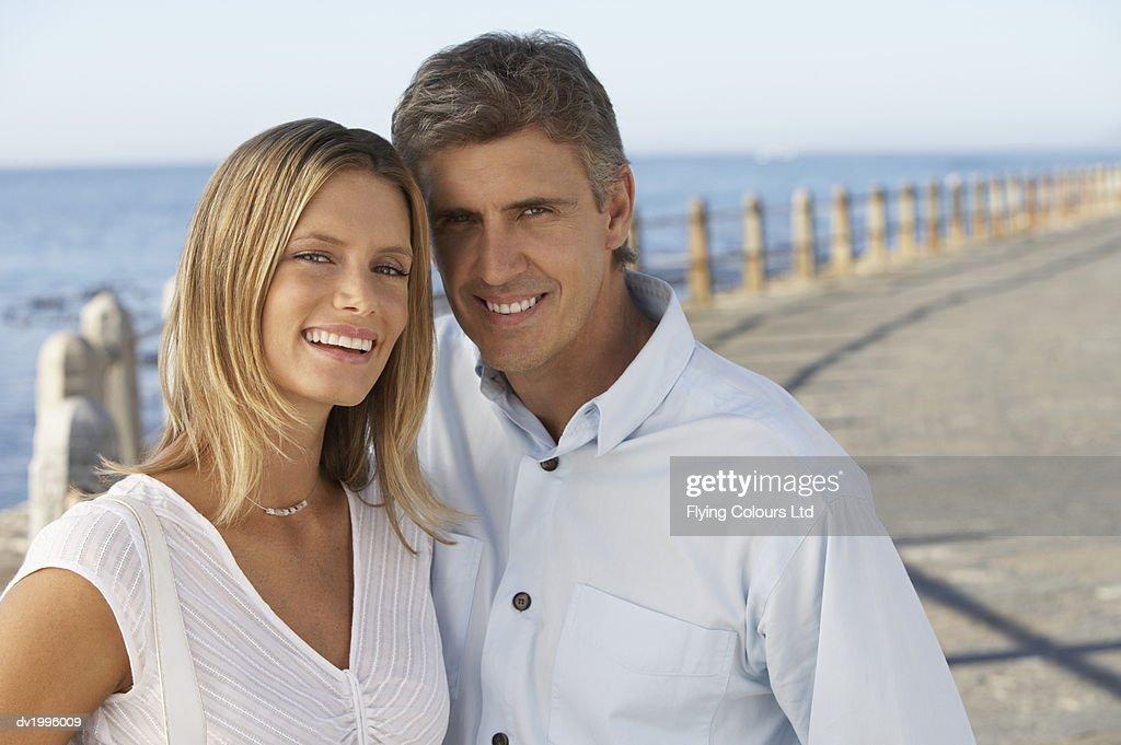 Thirtysomething Couple Standing on a Coastal Promenade : Stock Photo