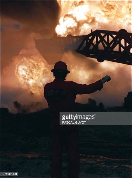 This 01 April, 1991 file photo shows a member of the Paul 'Red' Adair fire fighting crew working on a blown-out well damaged by retreating Iraqi...