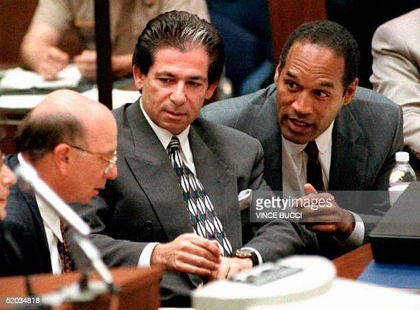 This 03 May 1995 file photo shows murder defendant OJ Simpson consulting with friend Robert Kardashian and Alvin Michelson the attorney representing...