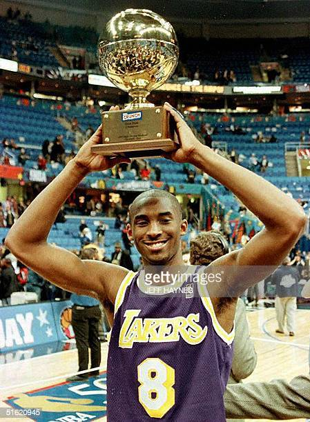 This 08 February file photo shows Kobe Bryant of the Los Angeles Lakers holding the trophy for winning the NBA Slam Dunk contest at Gund Arena in...