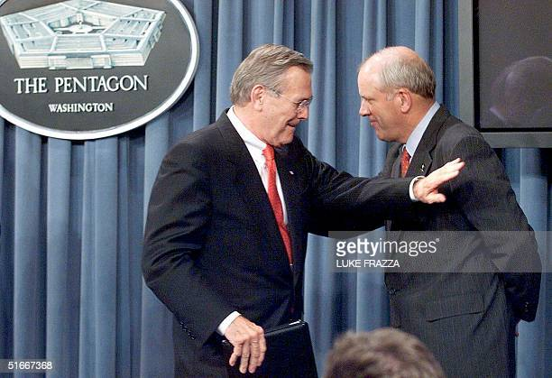 This 08 May 2002 file photo shows US Secretary of Defense Donald Rumsfeld tapping US Army Secretary Thomas White on the shoulder during a briefing at...