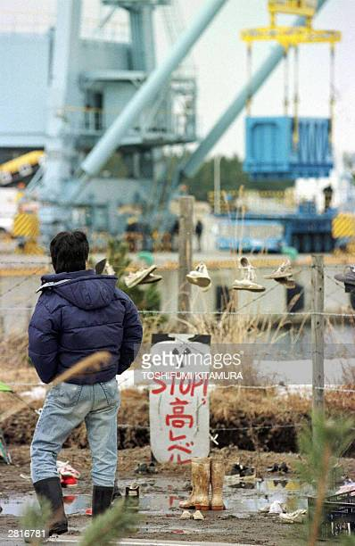 STORY JAPANNUCLEARPOWER This 09 March 1998 file picture shows an activist looking at a crane practicing loading a container onto a track at the Mutsu...