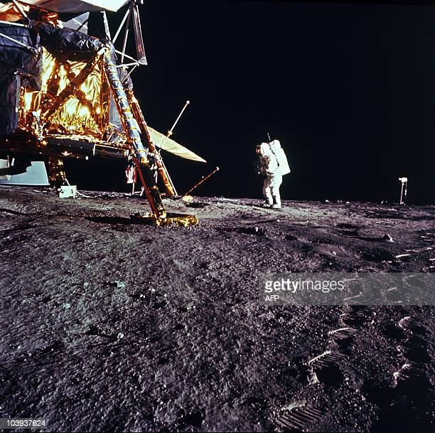 This 19 November 1969 file photo released by NASA shows one of the astronauts of the Apollo 12 space mission on the Moon standing by the Saturn V...