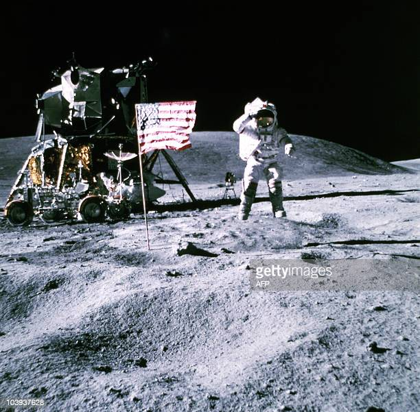 This 19 November 1969 file photo released by NASA shows one of the astronauts of the Apollo 12 space mission on the Moon standing by the US flag on...