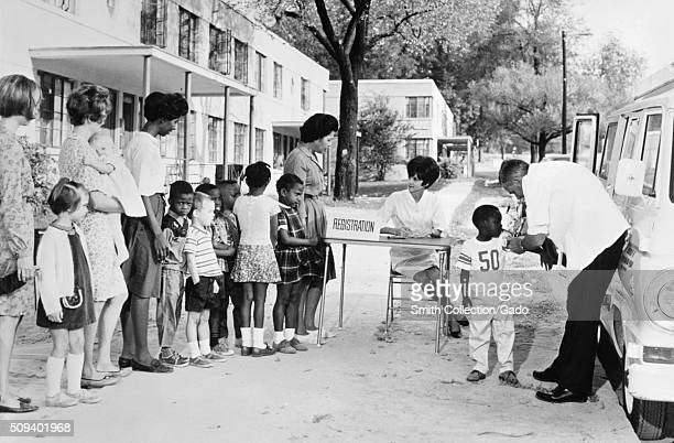 This 1976 photograph depicts a multiracial group of women and children in a housing project lining up at a mobile clinic waiting for, and receiving...
