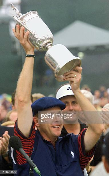 This 20 June 1999 file photo shows US golfer Payne Stewart holding up the US Open trophy after winning the major tournament in Pinehurst North...