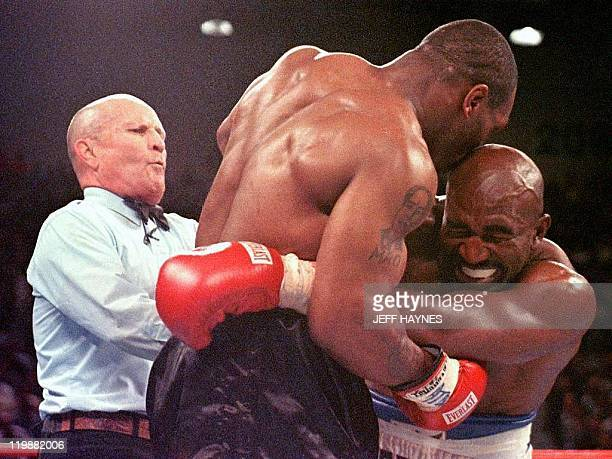 This 28 June 1997 file photo shows referee Lane Mills stepping in as Evander Holyfield reacts after Mike Tyson bit his ear in the third round of...