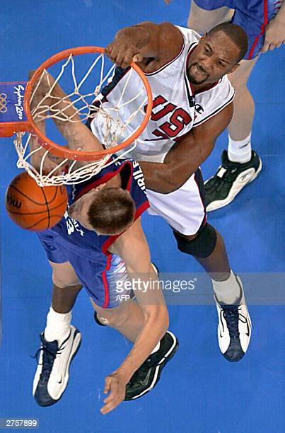 This 28 September 2000 file photo shows Alonzo Mourning of the US hanging onto the rim after dunking against Russia's Andrei Kirilenko at the...