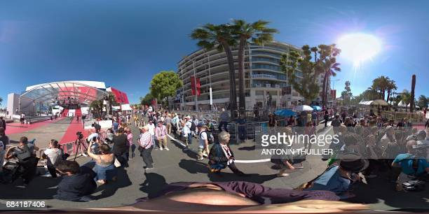 This 360 picture shows people outside the Palais des Festivals in the southeastern French city of Cannes on May 17 2017 as the red carpet is laid out...