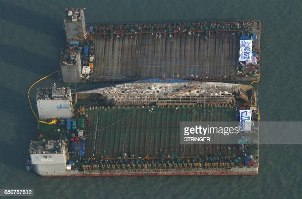 TOPSHOT This aerial image shows part of the damaged Sewol ferry between two barges after being raised during a salvage operation at sea off the...