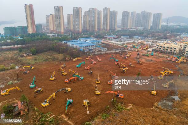 TOPSHOT This aerial photo on January 24 2020 shows excavators at the construction site of a new hospital being built to treat patients from a deadly...