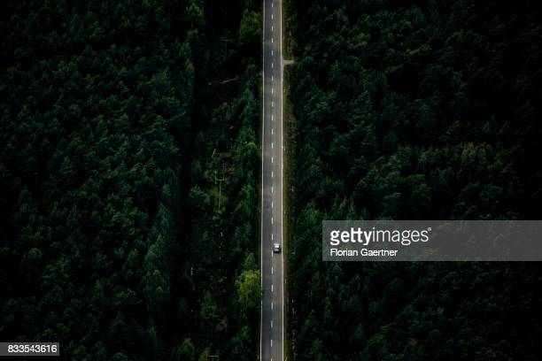This aerial photo shows a car driving on a country road through a forest on August 04 2017 in Bernsdorf Germany