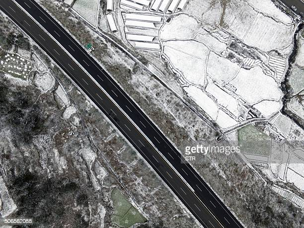This aerial photo shows a part of a highway closed due to cold and snow in Shaoguan south China's Guangdong province on January 24 2016 Much of China...