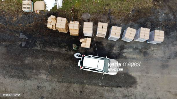 This aerial photo shows a volunter loading a food crate into a trunk as cars line up to pick up food boxes distributed through USDA's Farmers to...