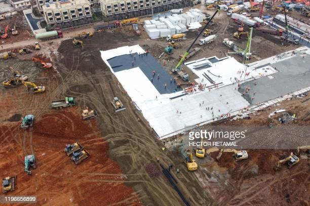 TOPSHOT This aerial photo shows excavators and trucks at the construction site of a new hospital being built to treat patients from a deadly virus...