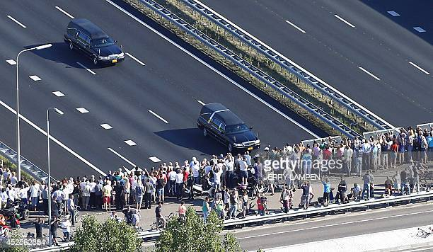 This aerial photo shows people watching from a bridge a convoy of hearses carrying coffins containing the remains of victims of the downed Malaysia...
