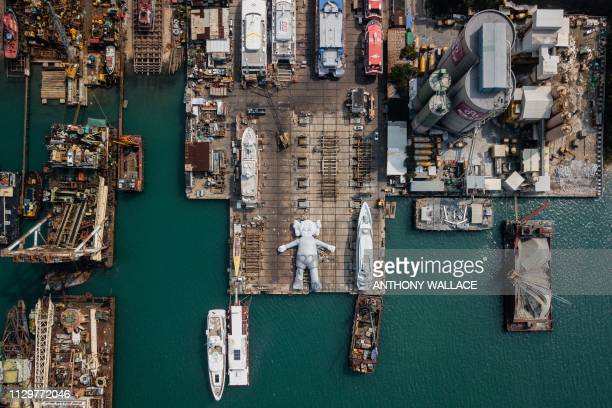 This aerial photo shows the 'KAWSHOLIDAY' 'Companion' inflatable sculpture by US artist and designer Brian Donnelly known professionally as Kaws in a...