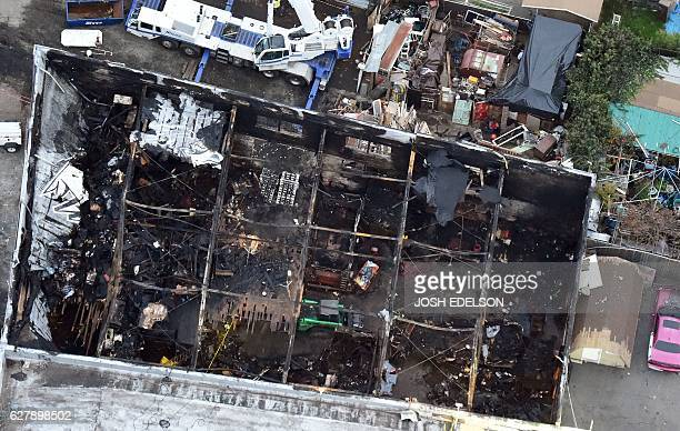 This aerial photo shows the remains of a fire ravaged warehouse on December 05 2016 that killed at least 36 people in Oakland California The death...