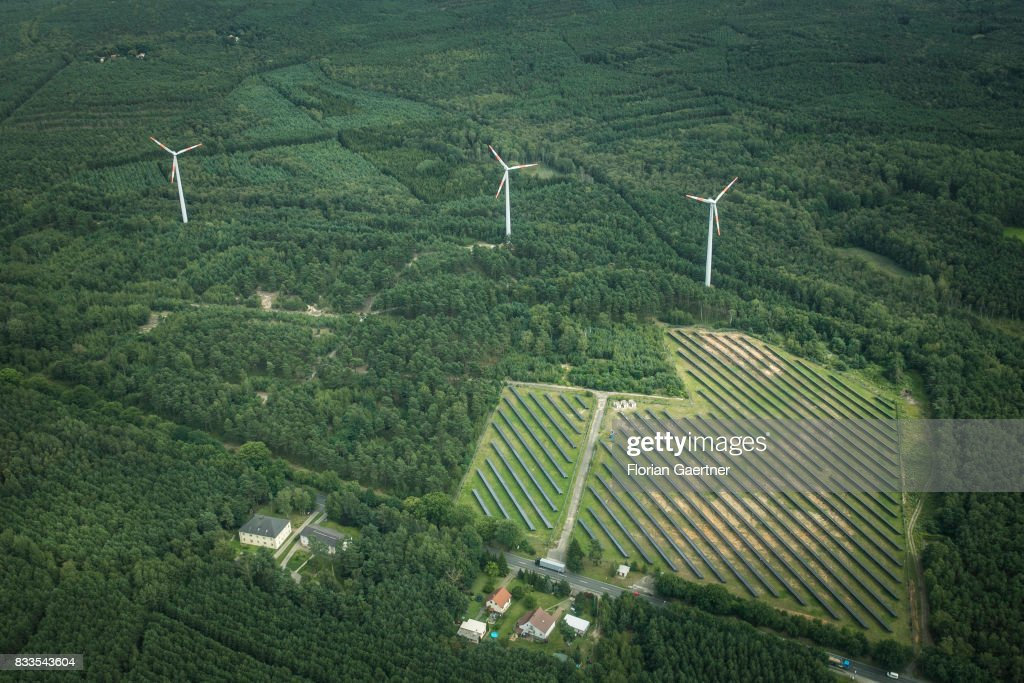 This aerial photo shows wind power stations next to a solar fields on August 04, 2017 in Bernsdorf, Germany..