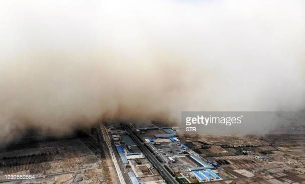 This aerial photo taken on April 25, 2021 shows a sandstorm engulfing a village in Linze county, in the city of Zhangye in China's northwestern Gansu...